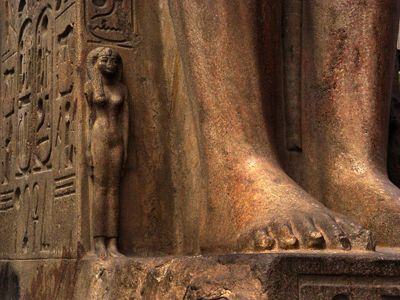 lovely small statue next to a gigantic feet in the Egyptian Museum in Cairo Egypt